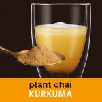 Chai Kurkuma im Glas. Löffel mit Chai Pulver im Vordergrund.